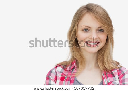 Blonde woman looking at camera while smiling against a white background - stock photo