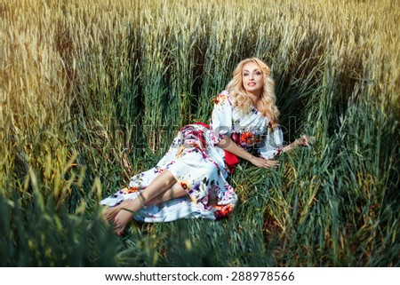 Blonde woman lying in a field.  Among the wheat ears. - stock photo