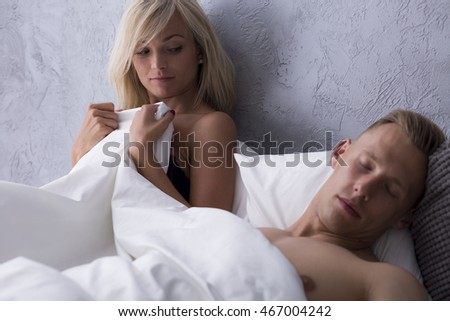 Blonde woman lying in a hotel bed with sleeping handsome man