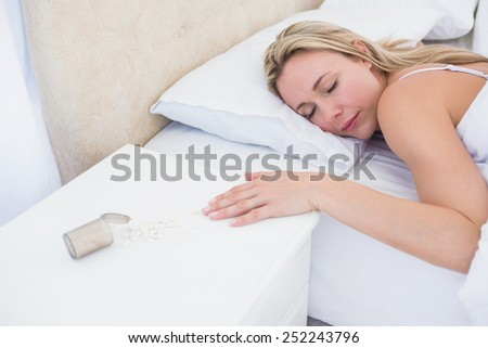 Blonde woman lying motionless in bed after overdose at home in the bedroom - stock photo