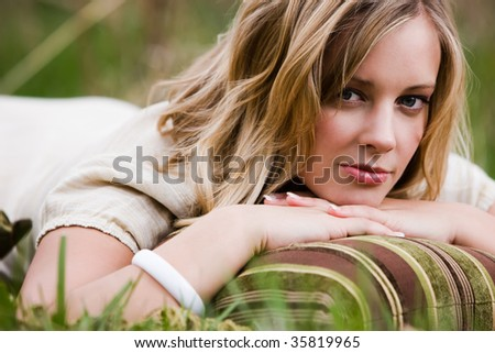 Blonde Woman lying on the grass on her stomach with a pillow - stock photo