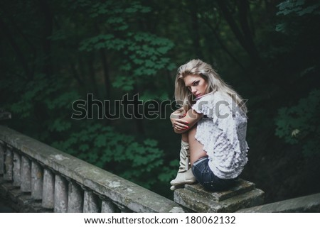 Blonde woman model posing and sitting on old vintage stone fence