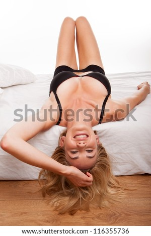 blonde woman on bed wearing black lingerie - stock photo