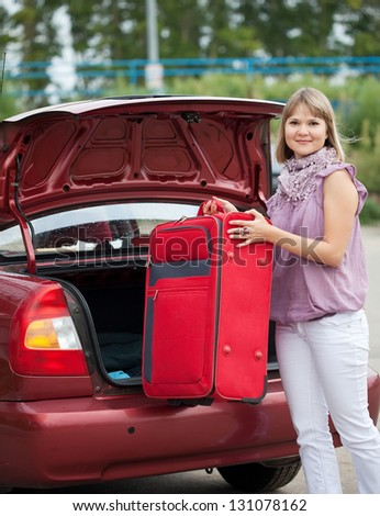 Blonde woman packing her baggage into the car - stock photo