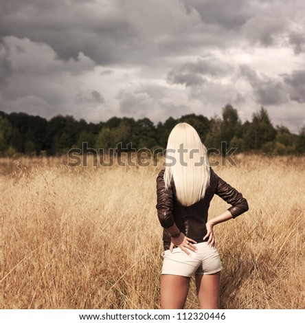 Blonde Woman Posing at the Field. Rear View - stock photo