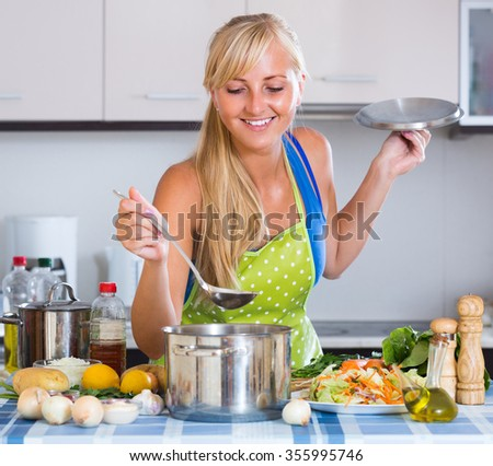 Blonde woman preparing healthy meal from vegetables at home kitchen