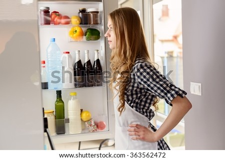 Blonde woman pulls out from the refrigerator products for dinner - stock photo