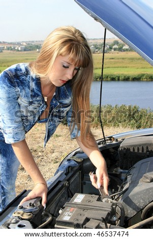 Blonde woman repairs car motor