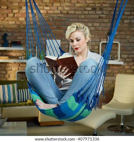 Blonde woman resting and reading in hammock like chair. - stock photo