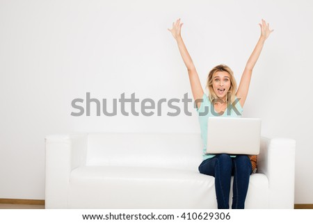 blonde woman sitting on her white sofa with laptop, searching a job - stock photo