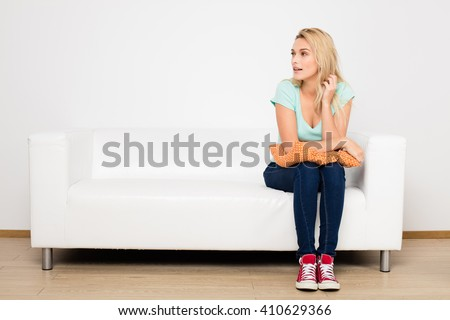 blonde woman sitting on her white sofa with pillow in hands - stock photo