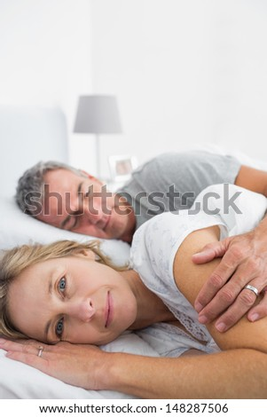 Blonde woman smiling at camera as husband is sleeping in bedroom at home