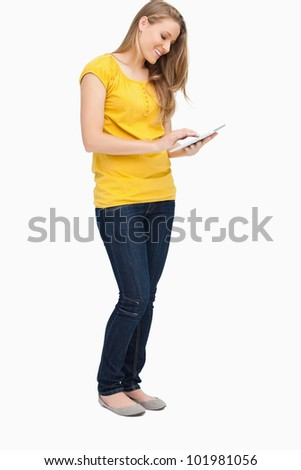 Blonde woman smiling while using a touch pad against white background - stock photo