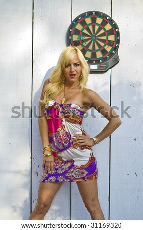 Blonde Woman standing in front of a Dart Board - stock photo