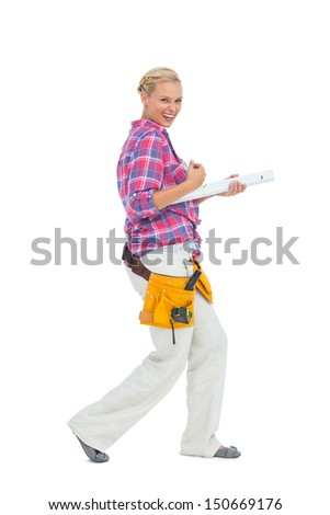 Blonde woman standing while playing with a spirit level on white background - stock photo