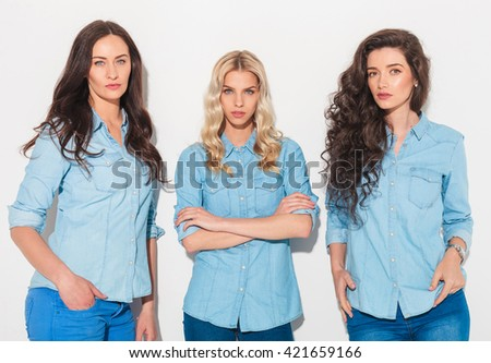 blonde woman standing with hands crossed near her friends in studio - stock photo