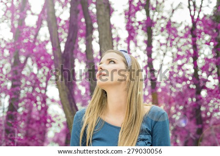 Blonde woman staring up in purple woods - stock photo