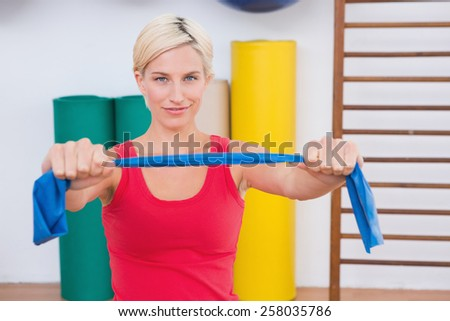 Blonde woman stretching arms in fitness studio - stock photo