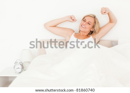 Blonde woman stretching her arms in her bedroom - stock photo