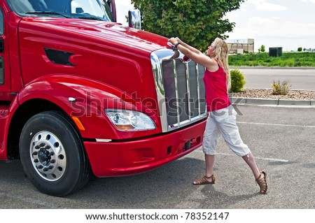 Blonde woman truck driver opening the hood on a semi-truck. - stock photo