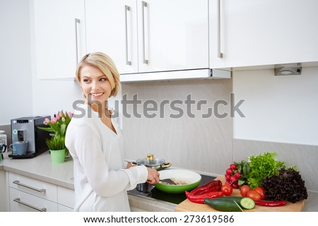 Blonde woman using a tablet computer to cook in her kitchen - stock photo