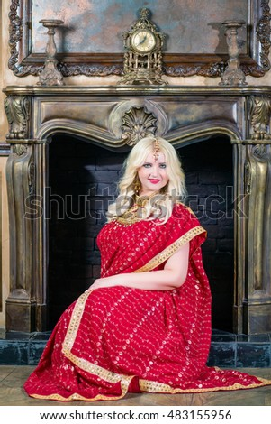 Blonde woman with decoration on head in red dress sits at fireplace in room.