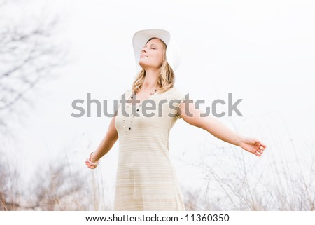 Blonde woman with hat standing outside with her face up and arms out basking in the sun - stock photo
