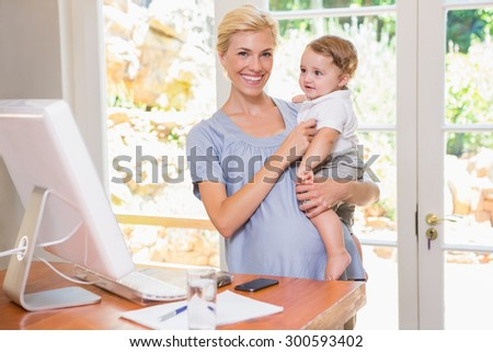 Blonde woman with his son using computer in the office - stock photo