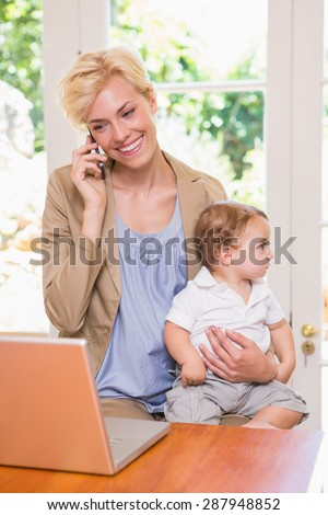 Blonde woman with his son using phone and laptop in the office - stock photo