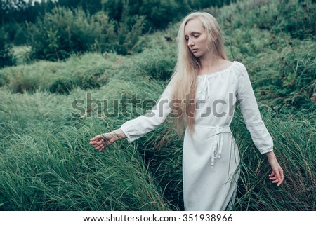 blonde woman with long hair in the morning fog , touching the grass - stock photo