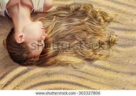 Blonde Woman with Long Wavy Hair on the Sea Sand. Natural Hair Care Cosmetics, Sun Bath in Tropic - stock photo