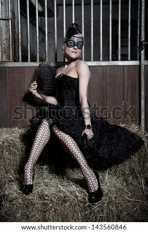 Blonde woman with mask in a stable - stock photo