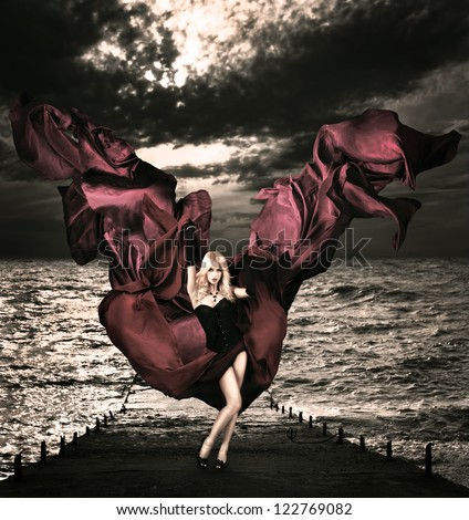 Blonde Woman with Waving Silk at Stormy Sea - stock photo