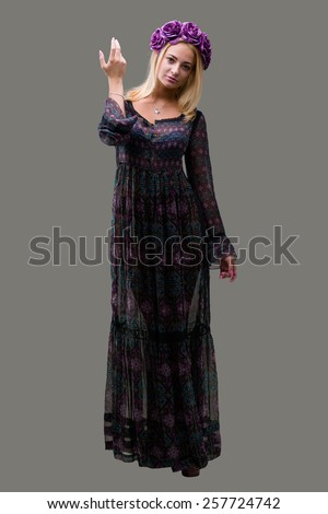blonde woman with wreath of flowers, full length portrait isolated over gray background - stock photo