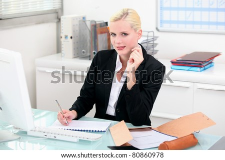 Blonde woman working at her desk - stock photo