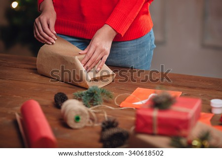blonde woman wrapping gifts on table, closeup hands, warm rustic style - stock photo