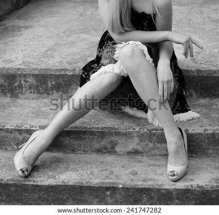blonde women sitting on stone stairs - stock photo