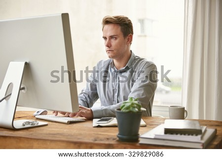 Blonde young businessman sitting at his office desk working and looking seriously at his screen while typing on his keyboard - stock photo