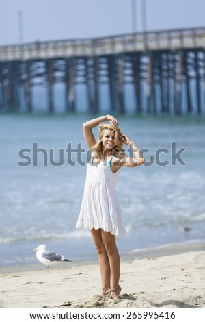 Blonde young female dancing and posing with both arms over her head on the beach - stock photo