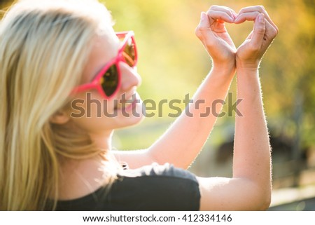 Blonde young girl holding hands in heart shape framing. Blonde woman posing outdoor.  - stock photo
