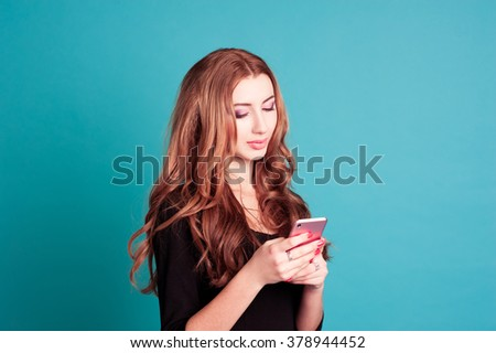 Blonde young girl 20-22 year old touching phone screen in room over blue. Calling. Texting message. - stock photo