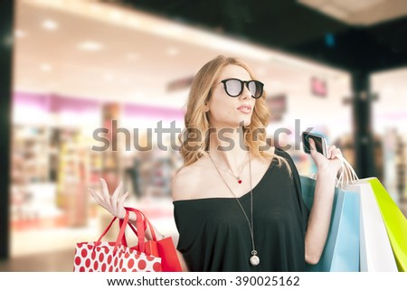 Blonde young woman holding colored shopping bags