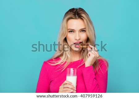 blonde young woman in pink blouse eating chocolate biscuit with milk on blue background - stock photo