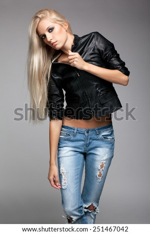 Blonde young woman in ragged jeans and black jacket on gray background