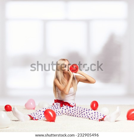 Blonde young woman sitting on white whole-floor carpet and inflating red balloon  near window - stock photo