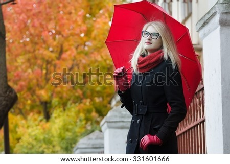 Blonde young woman with red fully collapsible umbrella and thumb in pocket is posing at autumn street background - stock photo