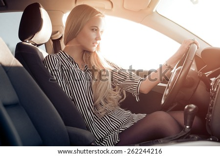 Blondie young girl at the wheel of sport car - stock photo