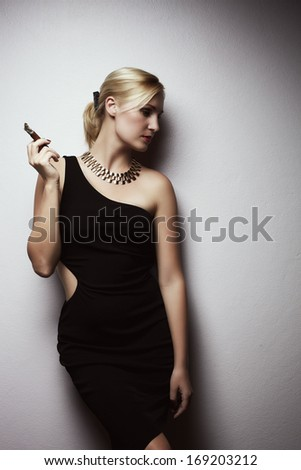 Blondy woman in black dress with cigar near wall