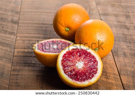 Blood oranges citrus fruit on table with cut half showing interior - stock photo