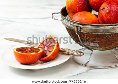 Blood oranges in a vintage metal strainer on white marble counter top. Sliced orange on a white plate with an antique silver fruit knife.